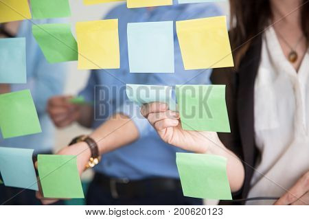 Midsection of business people sticking adhesive notes on glass wall in office