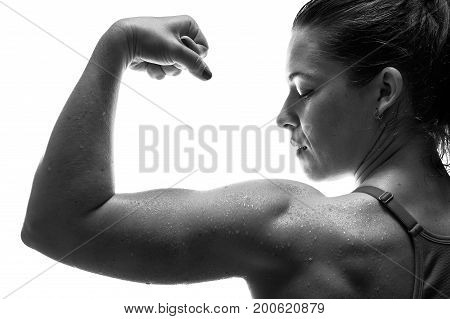 Rear view of strong muscular fitness female showing biceps muscle. Confident sporty woman posing on white background.