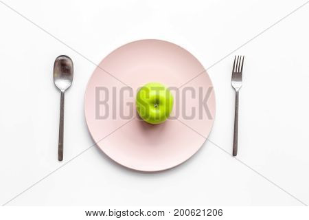 Slimming diet. Apple at plate on white background top view.