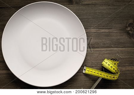 Losing weight. Diet. Empty plate and measuring tape on fork instead food on wooden background top view.
