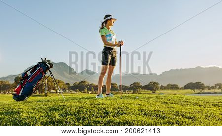 Full length shot of female golfer on golf course waiting to tee off. Young woman holding a golf club and looking at away on a sunny day.