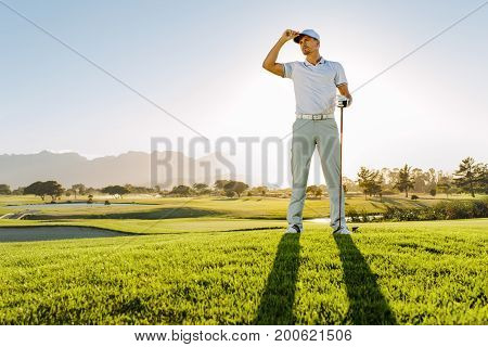 Professional Male Golfer Standing On Golf Course