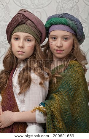beautiful little charming baby girls posing in bright fashionable clothes in oriental style