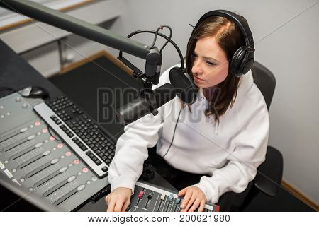 High angle view of young female jockey using music mixer while communicating on microphone in radio studio