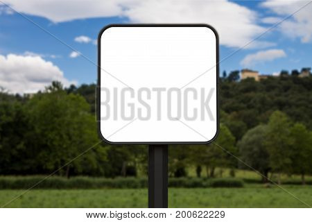 Square white sign with rounded corners. In the background a park and a hill with houses. The background is blurry.