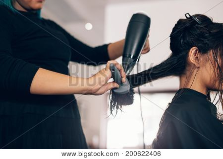 Female hairdresser using blower and brush to dry hair. Hair stylist using dryer on woman wet hair in salon.