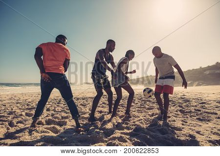 Friends Enjoying A Game Of Soccer At Beach