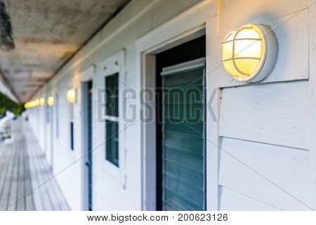 Row Of Hotel Or Motel Doors Outside With Illuminated Lights Lamps In Evening