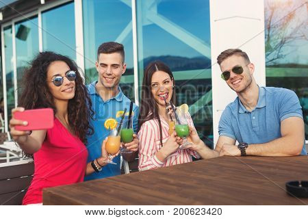 Friends having fun and drinking cocktails outdoor on a penthouse balcony make selfie photo