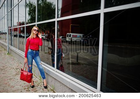 Portrait Of A Fabulous Young Woman In Red Blouse And Jeans Posing With Her Handbag And Sunglasses Ou