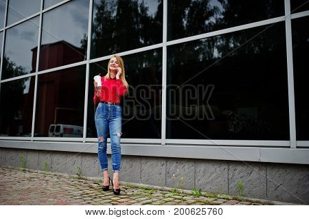 Portrait Of A Beautiful Woman In Red Blouse And Casual Jeans Talking On Mobile Phone And Holding A C
