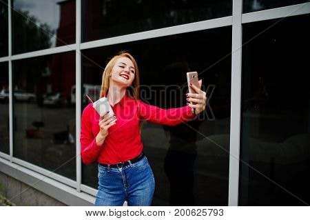 Portrait Of A Beautiful Woman In Red Blouse And Casual Jeans Taking Selfie On Mobile Phone And Holdi