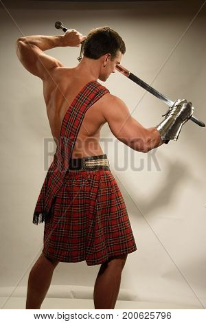 The hot highlander prepares for battle with a sword