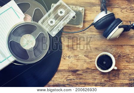 Retro music background vinyl records reel tape cassette headphones and cup of coffee on old wooden table
