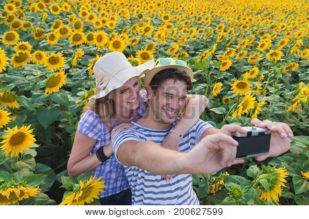Young heterosexual couple taking selfie in sunflower field by using retro vintage film camera. Love and summertime concepts.