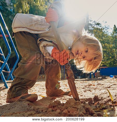 Cute boy having fun with sand and shovel on outdoor playground. Toned image with a square ratio