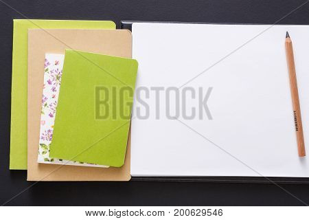 Stylish mockup with set of colorful notebooks, sketchbook and pencil on black background with copy space, flat lay, concept of start-up and stationery supplies