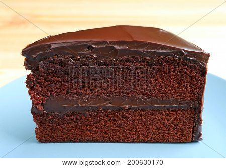 Front view of Chocolate Layer Cake Served on Wooden Table, Blurred Background