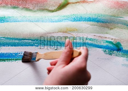 Artist creating watercolor painting. Expressive brush strokes of blue aquarelle on paper texture. Modern art backgroung with copy space