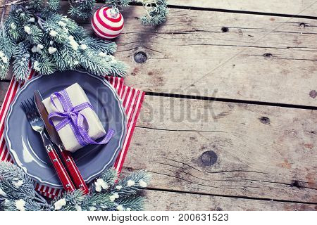 Christmas table setting. Grey plate knife and fork napkin and decorative candy cane on rustic wooden background. Top view. Place for text. Selective focus. Toned image.