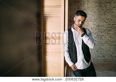 Thoughtful handsome guy in a white shirt and waistcoat near a window. Copy space. Close-up