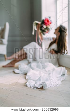 Blurred Image Of Cheerful, Young Bride Which Holds A Rustic Wedding Bouquet On Panoramic Window Back
