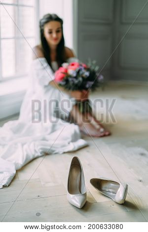 Wedding Shoes On A Blurred Background Of Cheerful, Young Bride Which Holds A Rustic Bridal Bouquet.