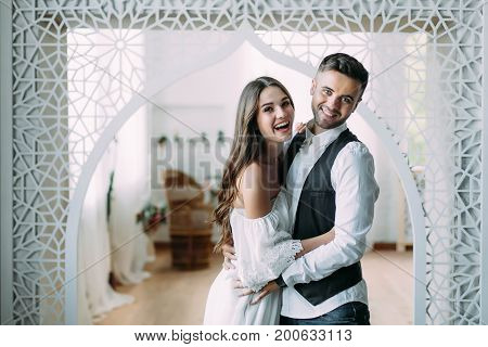 A Cheerful Bride And Groom With A Cute Smile Laughing And Embracing. Beautiful Newlyweds Posing In V