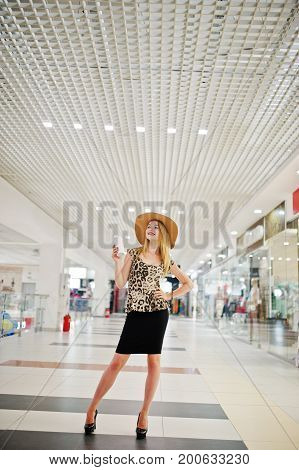 Portrait Of A Woman In Leopard Blouse, Black Skirt Posing In Shopping Mall With Hat And A Cup Of Cof
