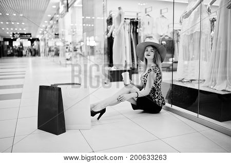 Portrait Of A Beautiful Woman In Leopard Blouse And Black Skirt Sitting On The Floor Drinking Coffee