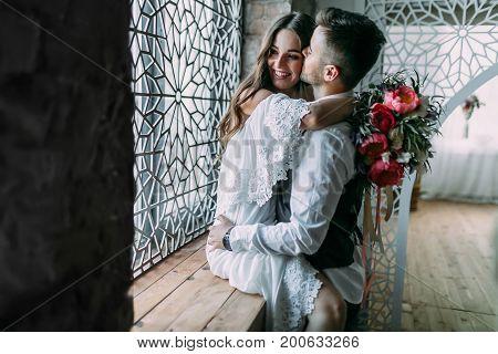 Cheerful Young Bride Hugging Groom While He Kisses Her In Cheek And Embraces Her Waist On The Window