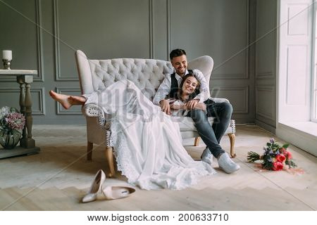 Young Bride In Tender Lace Dress Lies On Knees Of A Handsome Groom In Blue Jeans. Cheerful Newlyweds