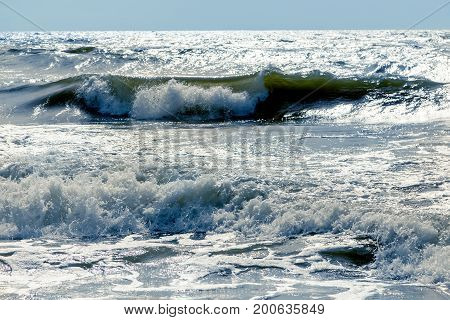 stormy baltic sea beach with waves under sunlight