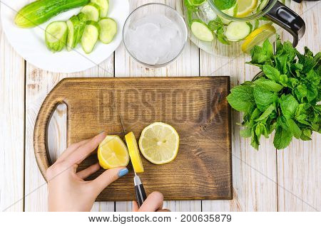 Sliced lemon on wooden cutting board prepared for lemonade.