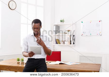 Concentrated african-american businessman in office, searching for new ideas on tablet
