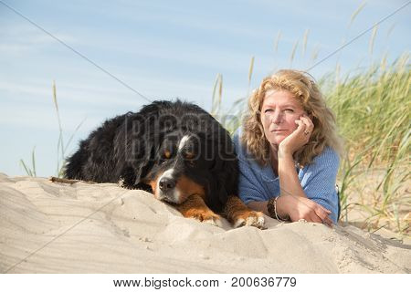mature woman with her dog on sand and grass lying