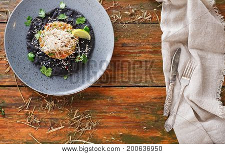 Exclusive restaurant food. Hawaiian appetizer - poke of fresh salmon on black flat cake and cutlery on linen cloth, served in rural style. Healthy meals on wooden background, top view, copy space