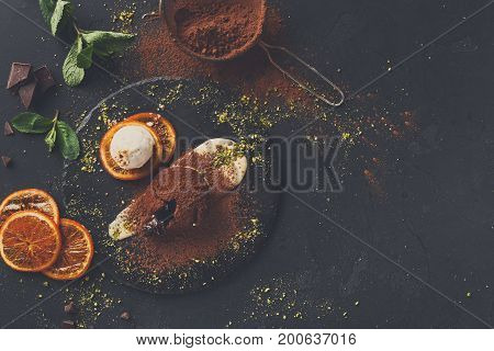 Exquisite french dessert. Chocolate fondant with creme anglaise and vanilla ice cream on round slate with orange citrons. Black background with cocoa, mint and sieve, top view, copy space