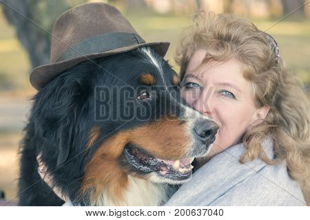 woman with bernese mountain dog on nature