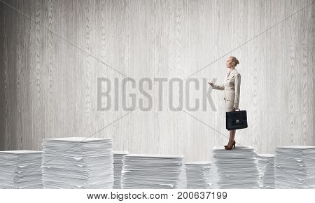 Confident business woman in suit standing on pile of documents with grey wall on background. Mixed media.