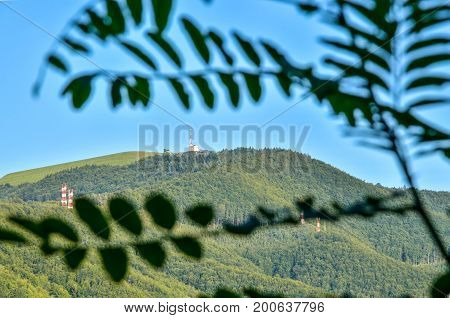 Summer mountain landscape. Green mountain with antenna tower in frame with blurred leaves.