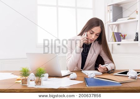 Serious business woman at work talking on phone and taking notes, sitting at her working place in office, copy space
