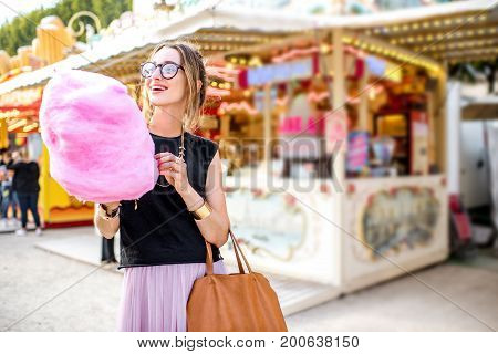 Young woman walking with pink cotton candy outdoors at the amusement park