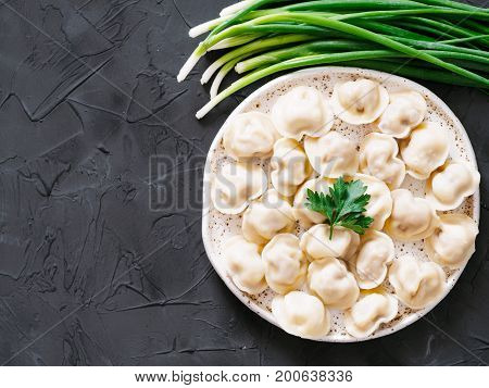 Traditional russian pelmeni, ravioli, dumplings with meat on black concrete background. Copyspace. Top view or flat lay. Russian food and russian kitchen concept.