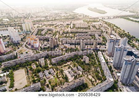 Residential district in a large metropolis with road junctions and houses. View of a newly built residential complex with a shopping center on the lower floors. Aerial view. From above. Property with panoramic views, near the river