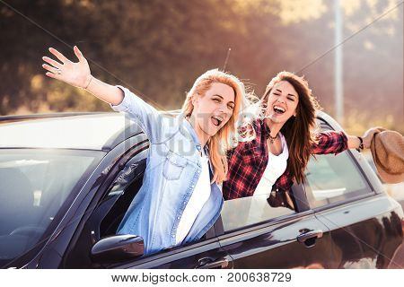 Two happy women in car concept of carefree roadtrip.