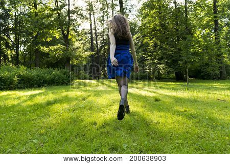 girl a woman in a blue skirt and long hair running through a meadow of green grass towards the trees