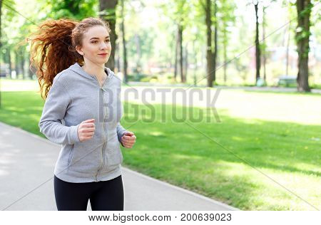 Young sporty woman running in green park during morning workout, copy space