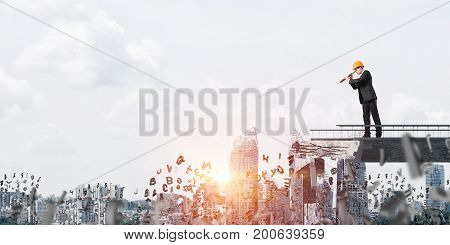 Young engineer in suit and helmet looking in spyglass while standing among flying letters on broken bridge with cityscape and sunlight on background. 3D rendering.