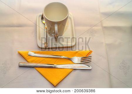 Close up teacup knife and fork on orange napkin on white table
